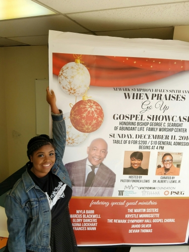 """Producer Flisadam standing next the the official window poster for the 6th annual When Praises Go Up Gospel Showcase designed by her printed by Newark Illustrated waering a Kernelius Maximus original print tee """"We The People""""."""